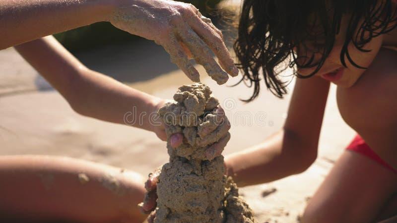 Jugendliche, Bruder und Schwester, die ein Sandburg auf einem tropischen Strand machen stockbild