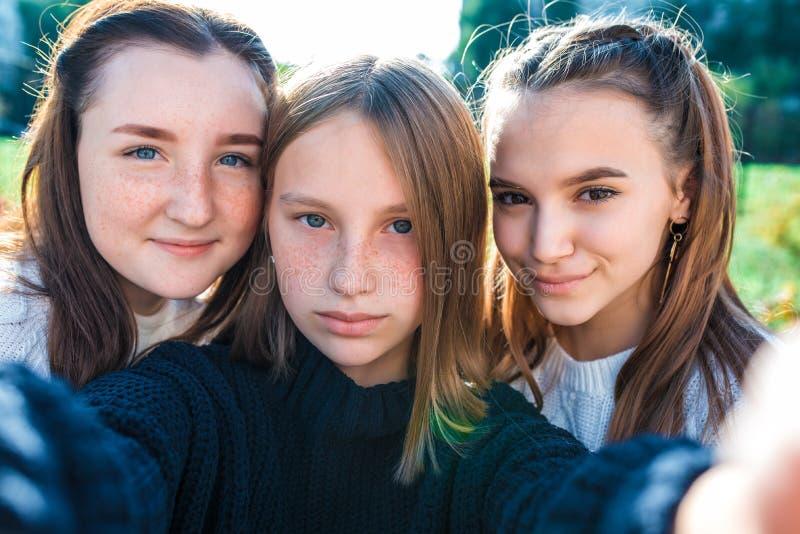 Jugendliche in der Nähe, 3 Schulmädchen, Freundinnen, Sommer, HerbstFrühling in der Stadt, Fotos machen Smartphone, online stockfotos