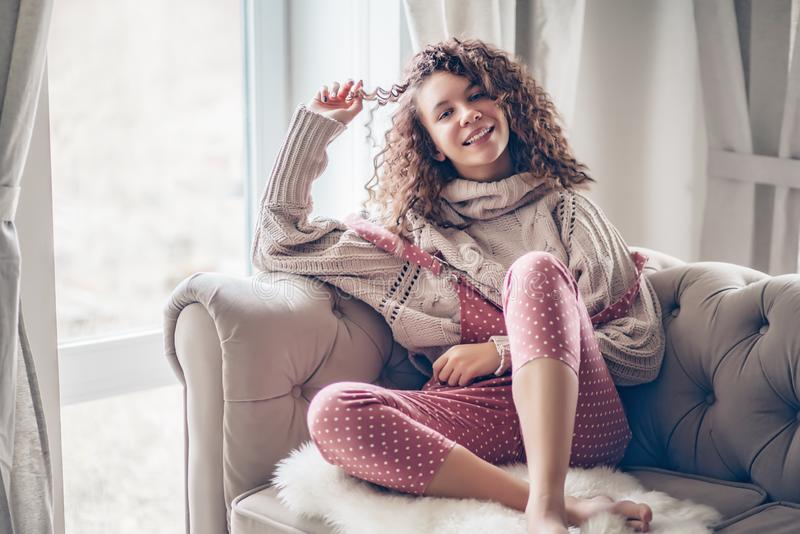Jugendliche in der Strickjacke und im Overall auf einer Couch lizenzfreies stockfoto