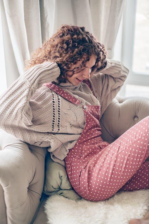 Jugendliche in der Strickjacke und im Overall auf einer Couch stockfotografie