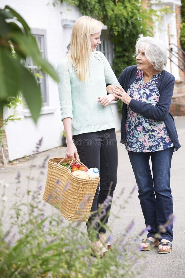 Jugendliche, die älterer Frau zu Carry Shopping hilft lizenzfreies stockfoto