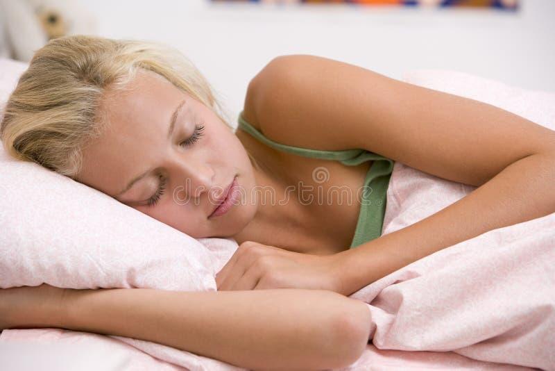 Jugendliche, die auf ihrem Bett liegt stockbilder
