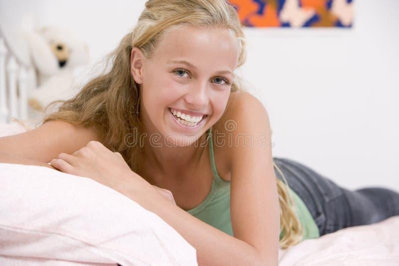 Jugendliche, die auf ihrem Bett liegt lizenzfreie stockfotografie