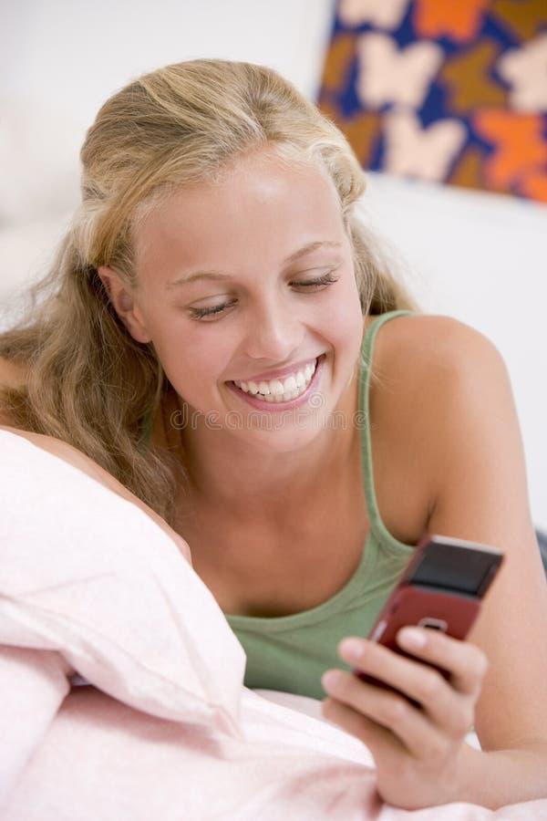 Jugendliche, die auf ihrem Bett unter Verwendung des Handys liegt lizenzfreie stockfotografie