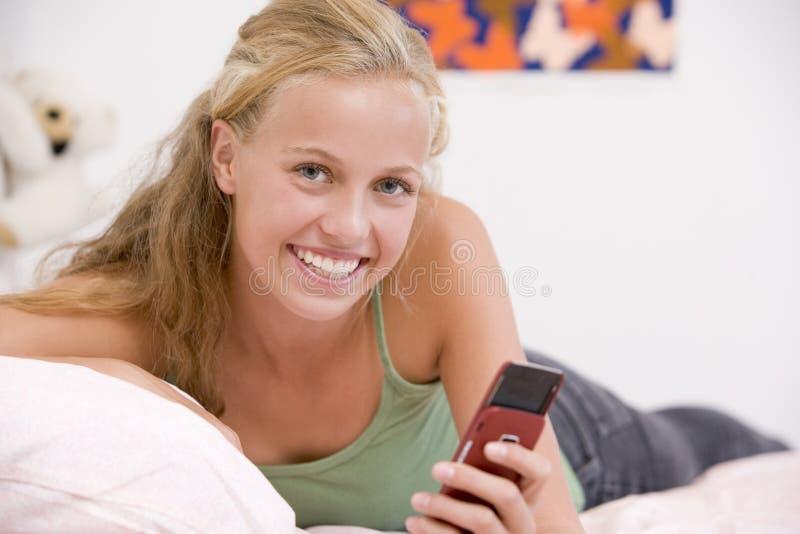 Jugendliche, die auf ihrem Bett unter Verwendung des Handys liegt stockfotos