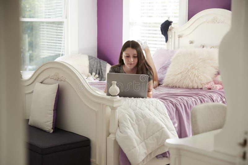 Jugendliche, die auf ihrem Bett unter Verwendung einer Laptop-Computers liegt lizenzfreie stockfotografie