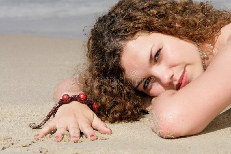 Jugendliche, die auf Sand liegt lizenzfreie stockfotografie