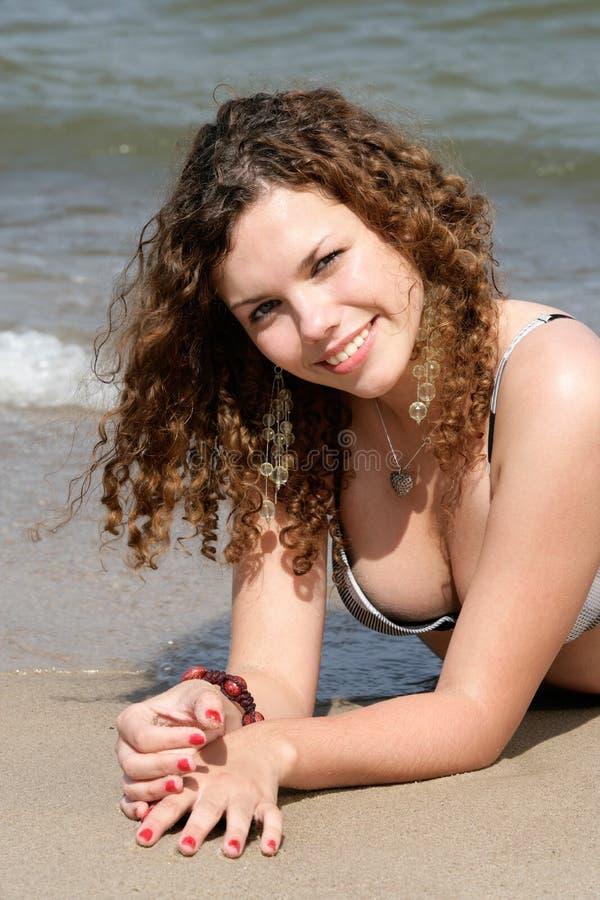 Jugendliche, die auf Sand liegt stockfotografie