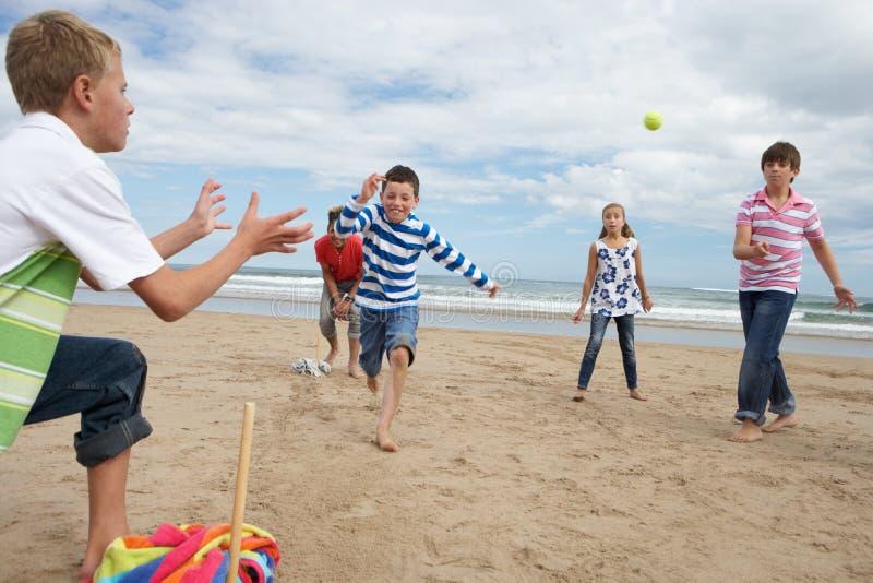 Jugendliche, die Baseball auf Strand spielen stockbilder