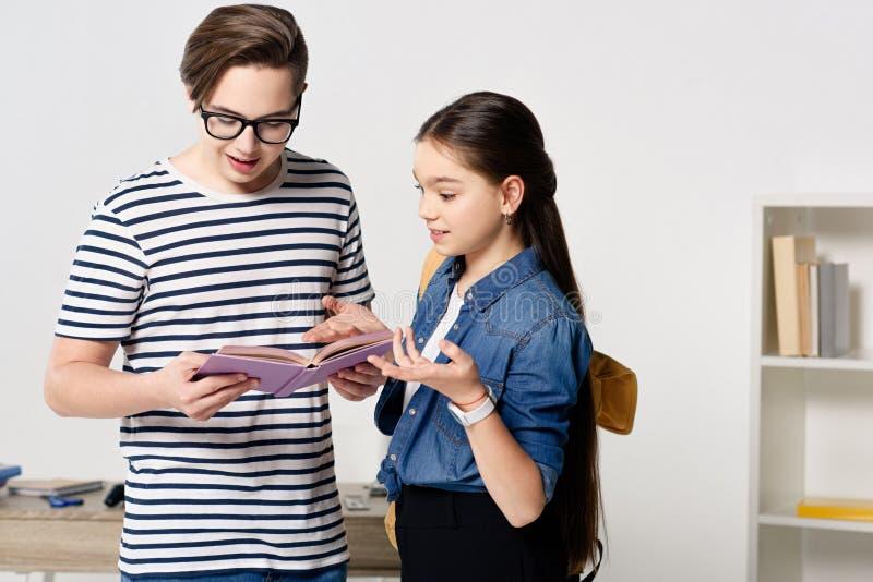 Jugendliche, die Buch und das Gestikulieren betrachten stockbild
