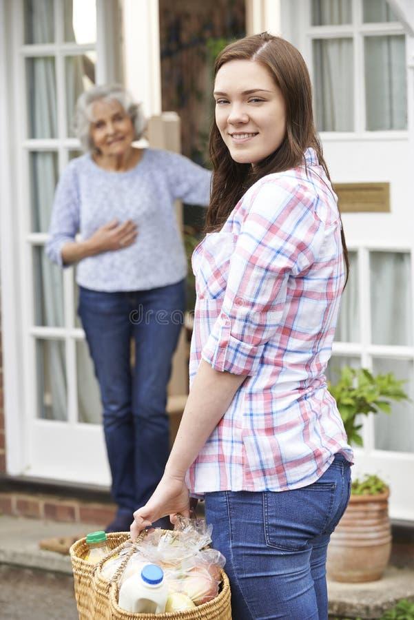 Jugendliche, die das Einkaufen für ältere Frau tut lizenzfreies stockfoto