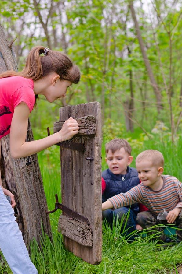 Jugendliche, die das Spielen mit zwei Jungen aufpasst stockbilder