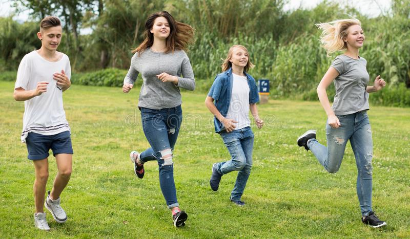 Jugendliche, die durch grünen Rasen im Sommer im Park laufen lizenzfreies stockfoto