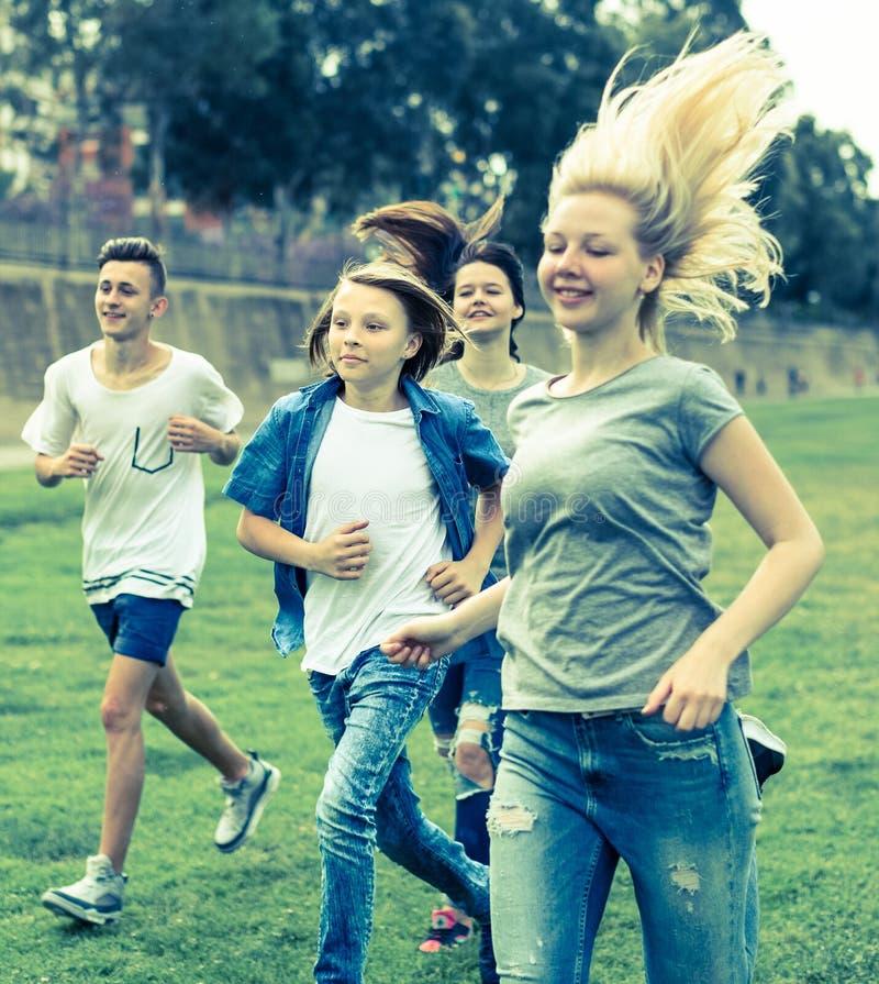 Jugendliche, die durch grünen Rasen im Sommer im Park laufen lizenzfreies stockbild