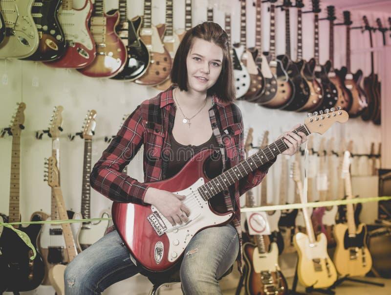 Jugendliche, die E-Gitarre wählt stockbilder
