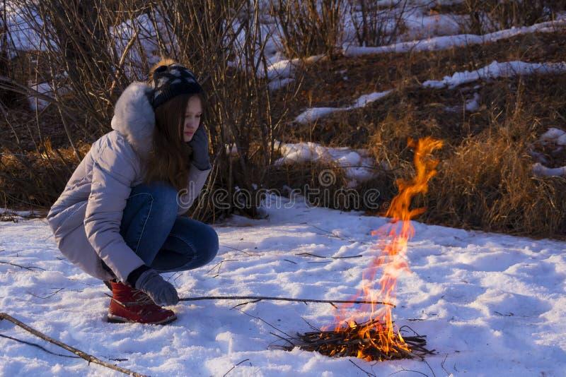 Jugendliche, die an einem Feuer im Schnee unter den Feldern im Winter sitzt lizenzfreie stockbilder
