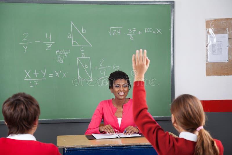 Jugendliche, die Hand während Lehrer Looking At anhebt stockfotografie