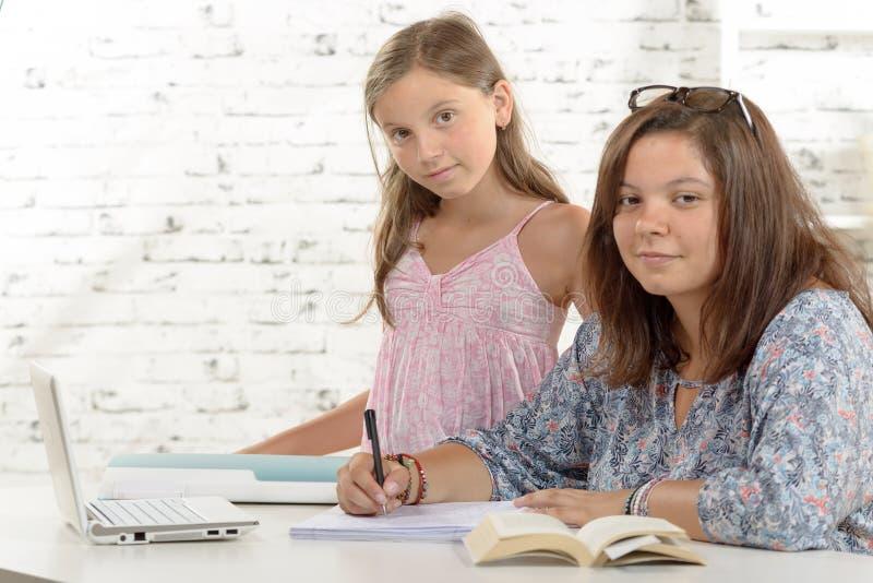 Jugendliche, die ihre Hausarbeit mit ihrer kleinen Schwester tut lizenzfreies stockbild
