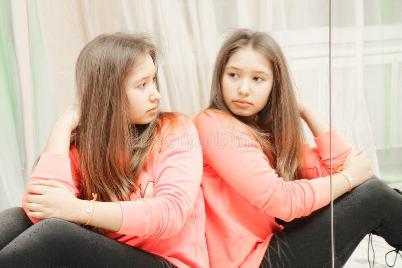 Jugendliche, die ihre Reflexionsnahaufnahme betrachtet stockfotografie