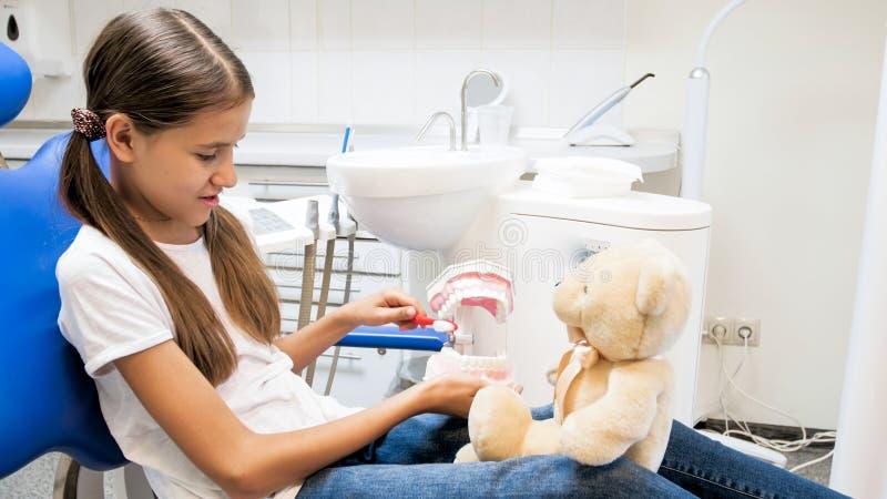 Jugendliche, die ihrem Teddybären zeigt, wie man richtig Zähne säubert stockfoto