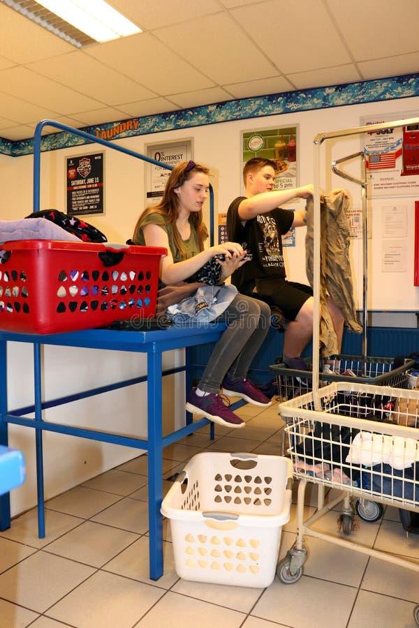 Jugendliche, die Kleidung in einem Waschautomaten falten lizenzfreies stockbild