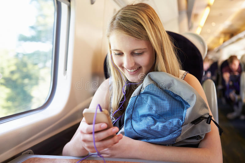 Jugendliche, die Musik auf Zug-Reise hört lizenzfreies stockfoto
