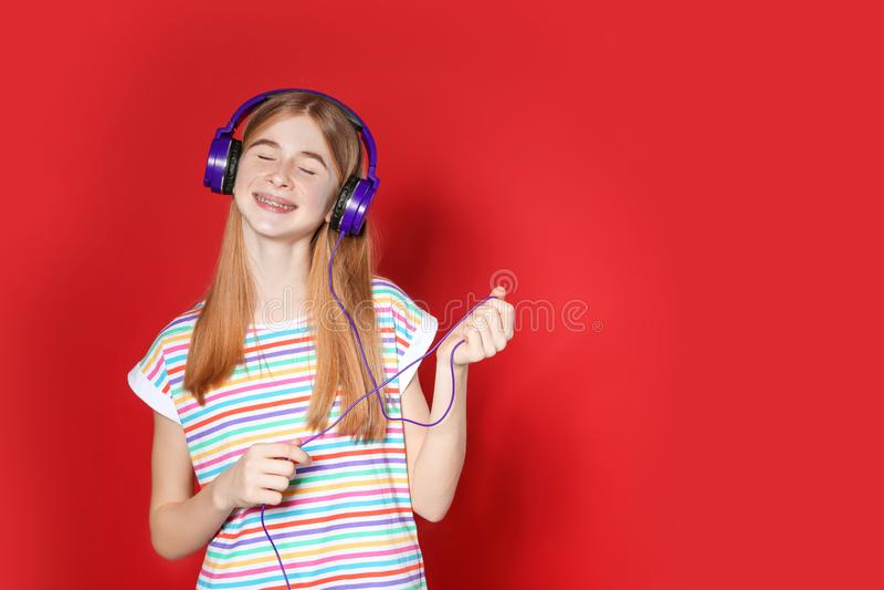 Jugendliche, die Musik in den Kopfhörern auf Farbhintergrund genießt stockbilder