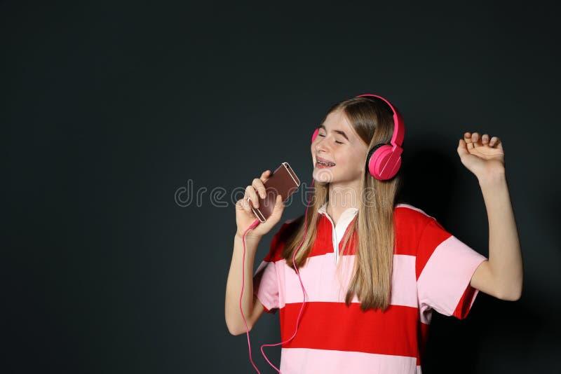Jugendliche, die Musik in den Kopfhörern auf Schwarzem genießt Raum f?r Text lizenzfreie stockfotos
