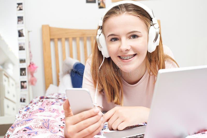 Jugendliche, die Musik hört, während, Handy verwendend lizenzfreie stockfotografie