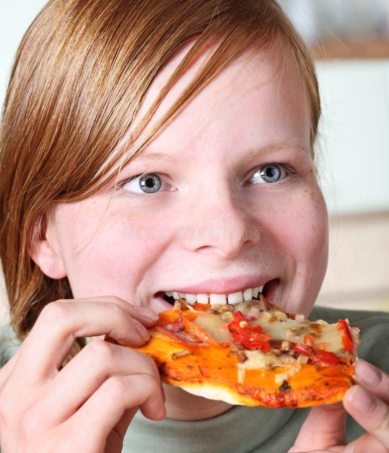 Jugendliche, die Pizza isst stockbilder