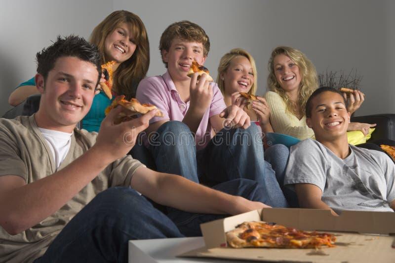 Jugendliche, die Spaß haben und Pizza essen stockbilder