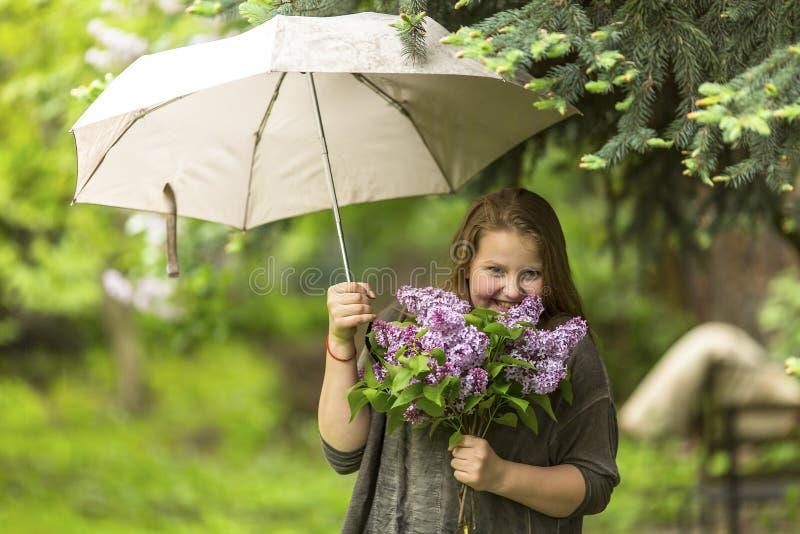 Jugendliche, die unter einem Regenschirm mit einem Blumenstrauß von Fliedern in ihrer Hand steht glücklich stockfotos