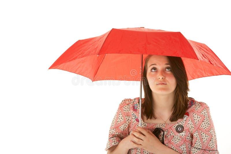 Jugendliche, die unter rotem Regenschirm steht lizenzfreie stockfotografie