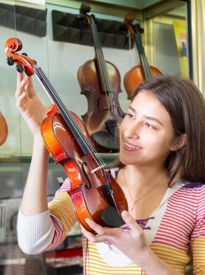 Jugendliche, die Violine im Speicher vorwählt lizenzfreie stockfotografie