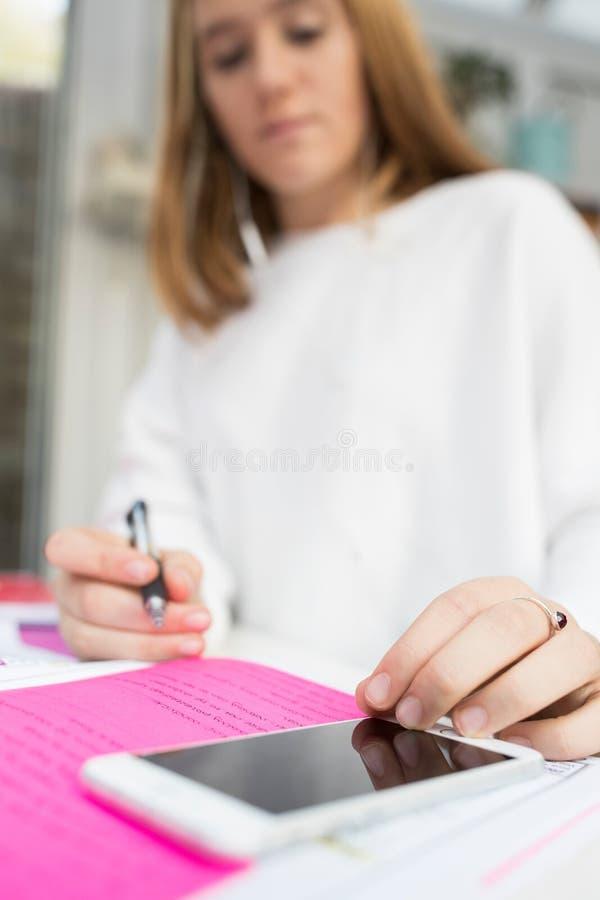 Jugendliche, die zu Hause studiert, während, Handy verwendend lizenzfreies stockbild