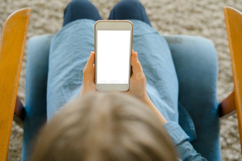 Jugendliche in einem blauen Kleid, das auf einem Lehnsessel beim Halten eines intelligenten Telefons mit einem leeren Bildschirm  lizenzfreie stockbilder