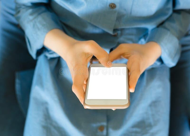 Jugendliche in einem blauen Kleid, das auf einem Lehnsessel beim Halten eines intelligenten Telefons mit einem leeren Bildschirm  lizenzfreie stockfotos