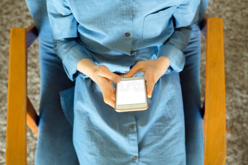 Jugendliche in einem blauen Kleid, das auf einem Lehnsessel beim Halten eines intelligenten Telefons mit einem leeren Bildschirm  stockbild