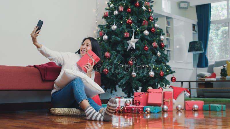 Jugendliche entspannen sich gerne mit Geschenken und mit Smartphone-Selfie mit Weihnachtsbaum genießen xi Winterferien stockfotografie