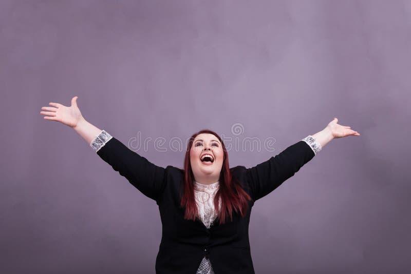 Jugendliche Geschäftsfrau im schwarzen Anzug bewaffnet weit offenes und hebt in die Luft an lizenzfreie stockfotografie