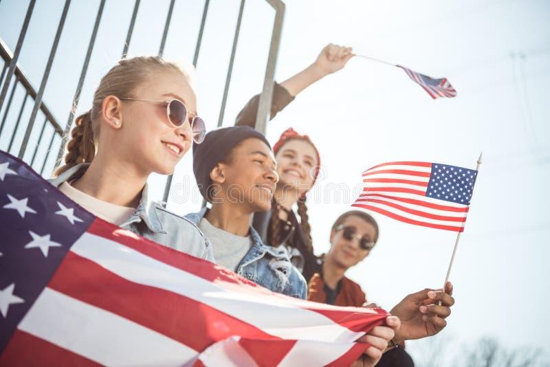 Jugendliche gruppieren Haben des Spaßes und das Wellenartig bewegen von amerikanischen Flaggen bei Sonnenuntergang lizenzfreie stockfotos