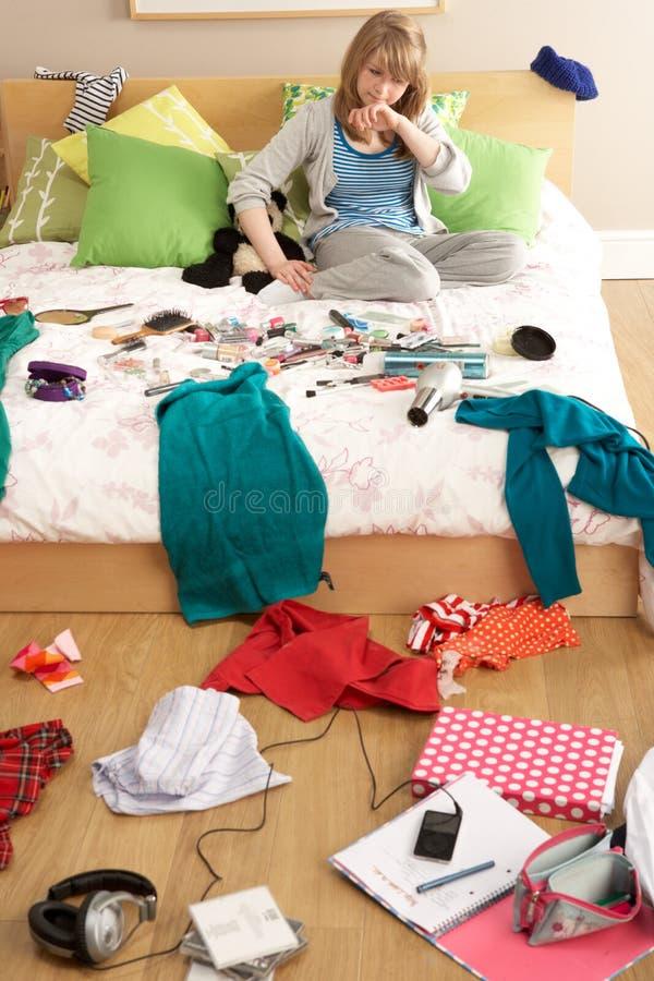 Jugendliche im unordentlichen Schlafzimmer lizenzfreie stockbilder