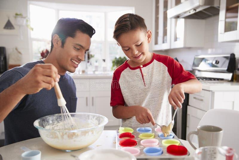 Jugendliche Jungenstellung am Tisch in der Küche, die Kuchen mit seinem Vater, Abschluss oben macht stockfotos