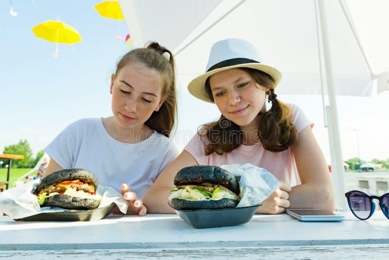 Jugendliche Mädchen mit großen schwarzen Burgern Sitzen Sie in einem Straßencafé, sonnigen in einem Sommertag in der Erholung und stockbild