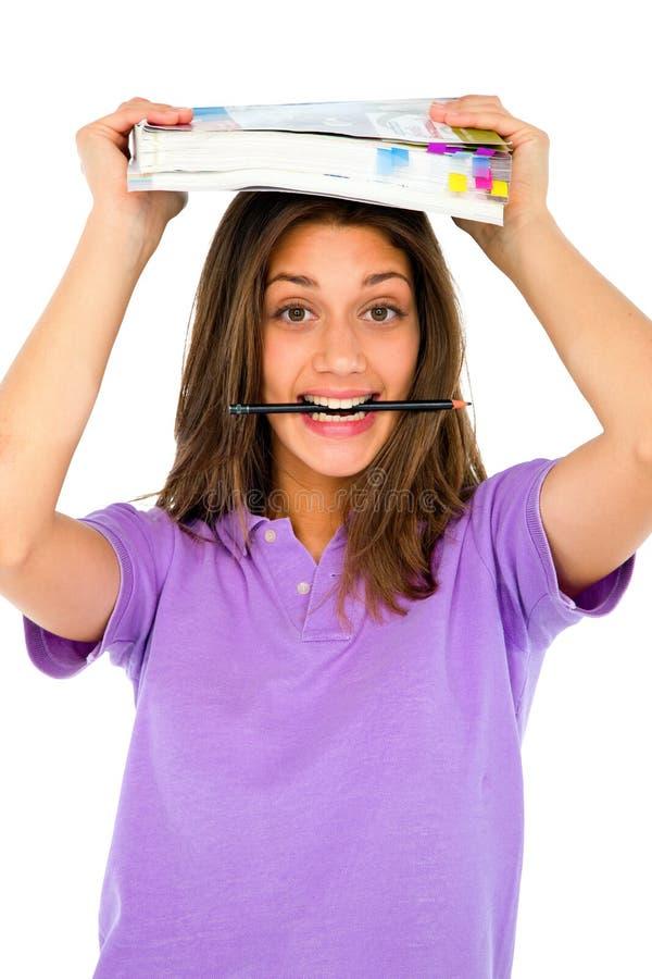 Jugendliche mit Bleistift im Mund und in den Büchern stockbilder