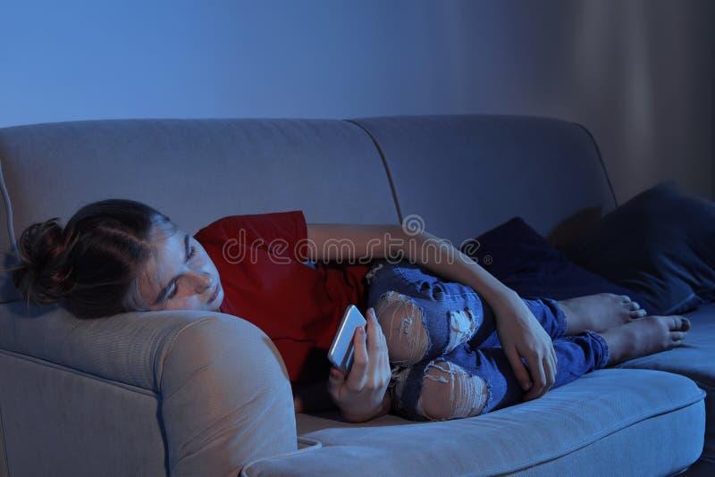 Jugendliche mit dem Smartphone, der auf Sofa liegt Gefahr des Internets lizenzfreie stockfotos