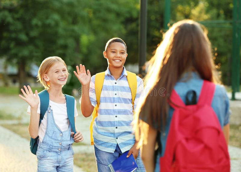 Jugendliche mit den Rucksäcken, die im Park sich treffen stockbild