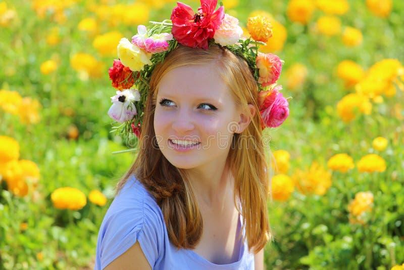 Jugendliche mit einem Kranz von bunten Blumen auf ihrem Kopf stockfotos