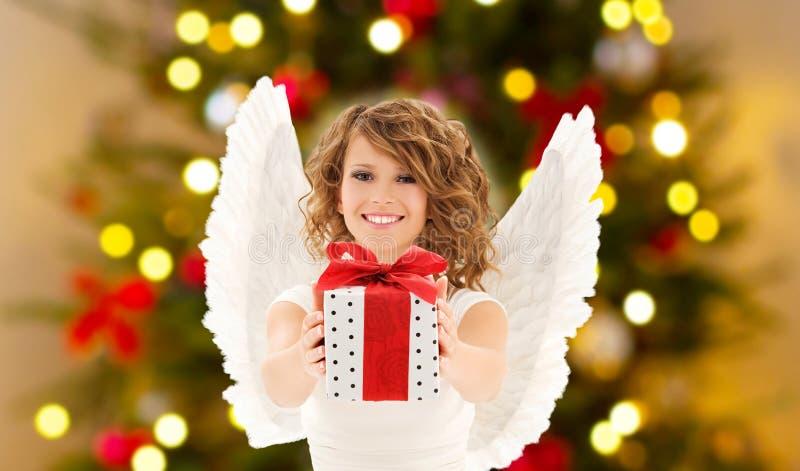 Jugendliche mit Engelsflügeln und Weihnachtsgeschenk lizenzfreie stockfotos