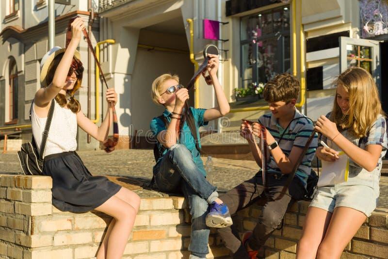 Jugendliche mit Filmfotonegativen des Interesses und der Überraschung aufpassenden, Stadtstraßenhintergrund stockbild